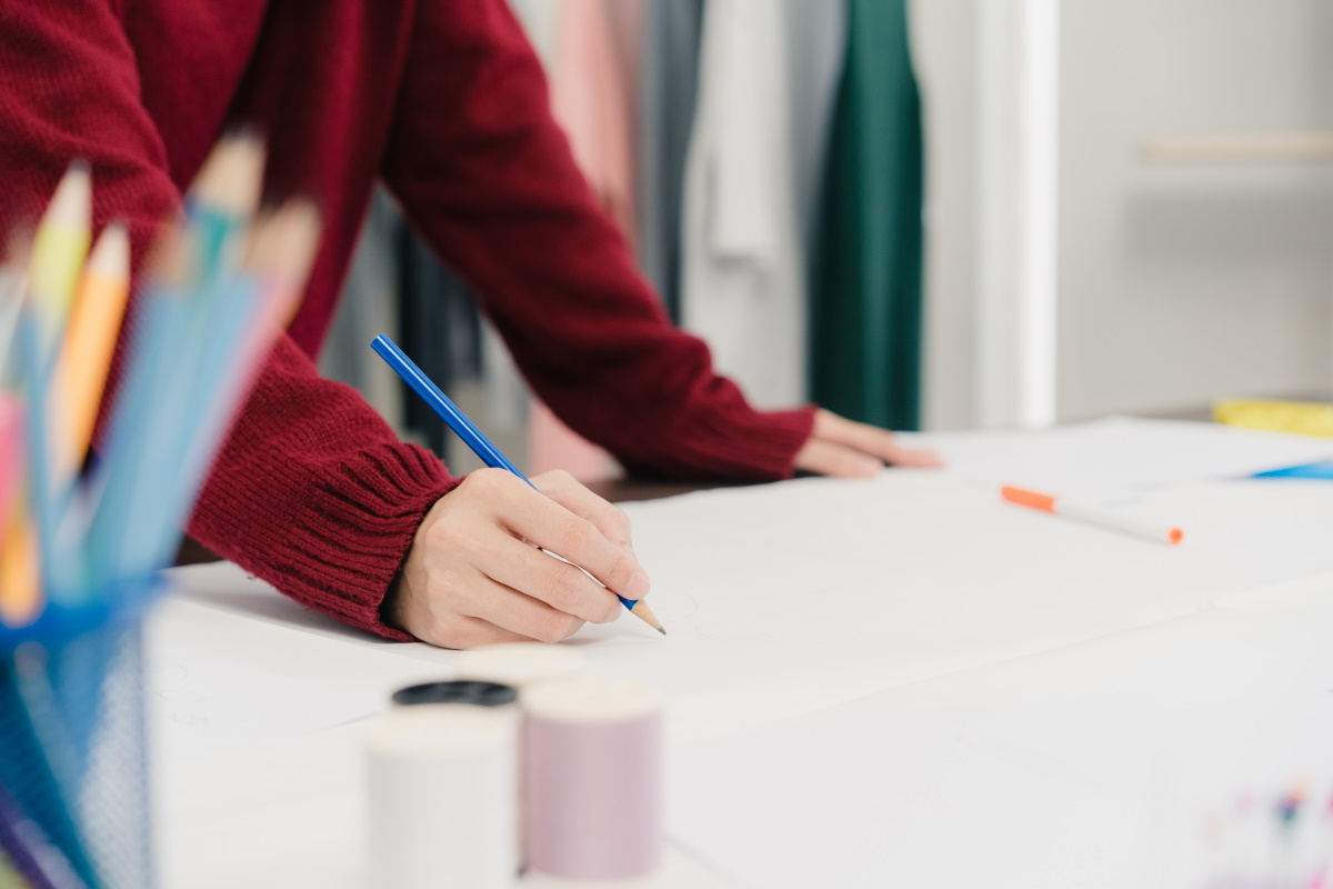 Professional beautiful Asian female fashion designer working with fabric sketches and drawing clothing design at the studio. Lifestyle women working concept.
